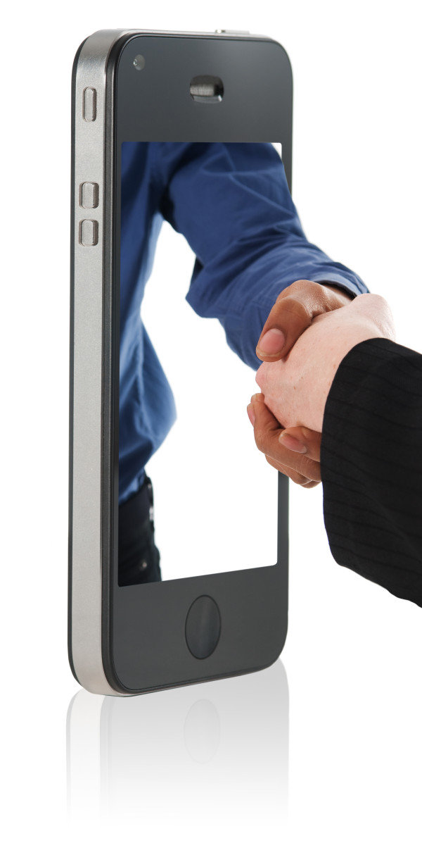 Hand Shake in Mobile Phone - hand shake deal over a smart phone